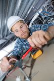 Electrician wiring in roof space. Electrician Royalty Free Stock Image