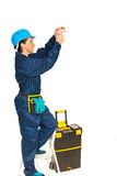 Electrician woman. Electrician worker woman changing a bulb isolated on white background stock images