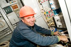 Electrician at work. One electrician working on a industrial panel mounting and assembling new wiring stock photography