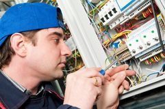 Electrician at work. One electrician working on a industrial panel mounting and assembling new wiring Stock Photo
