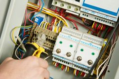 Electrician at work. One electrician working on a industrial panel mounting and assembling new wiring with plyers Royalty Free Stock Image