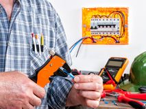 Electrician at work on cables with wire stripper. Electrician technician at work with wire stripper on cables in a residential electrical installation Royalty Free Stock Photo