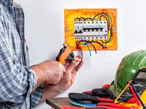 Electrician at work on cables with wire stripper. Electrician technician at work with wire stripper on cables in a residential electrical installation Stock Photos