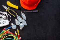 Electrician work concept. Hard hat, tools, cabel, bulb, socket outlet on black background top view space for text royalty free stock images