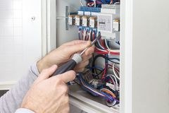 Electrician at work on an electrical panel royalty free stock photography