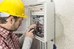 Electrician at work on an electrical panel royalty free stock images