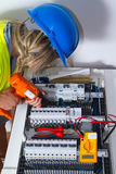 Electrician at work. Female electrician at work with electric devices, nowdays woman are more and more in the fields once of man Stock Photos