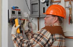 Electrician at work. With his instrument of measurement Stock Image