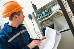 Electrician worker adjusting video surveillance system. Technician electrician worker agjusting examining electrical equipment of video surveillance camera Royalty Free Stock Photo