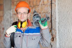Electrician worker with electrical cable and drill tool. Electrician man construction worker with electrical cable and puncher drill tool at house wall stock photo