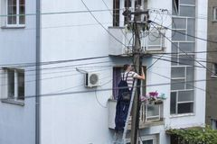 Electrician worker on ladder repair electrical system on electricity pillar or Utility pole stock photos