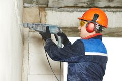 Electrician worker with perforator drill. Young handyman builder with electric drill perforator on duty Royalty Free Stock Image