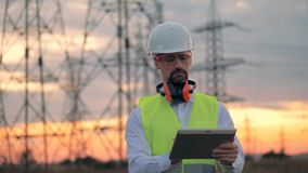 Electrician worker with tablet near power line. 4K stock footage