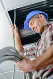 Electrician working in ceiling hatch. Electrician working in a ceiling hatch Stock Photography