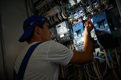 Electrician working during damage. Electrician worker detecting and fixing wire cabling damage breakdown with tester scredriver in power distribution fuseboard Royalty Free Stock Photos