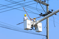 Electrician working on electric pole Stock Image