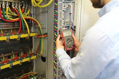 Electrician is working in electrical cables distribution fuse box with multimeter.  stock images