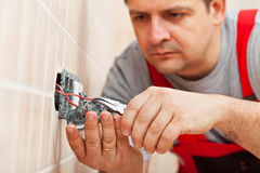 Electrician working on electrical wall fixture. Inserting the wires, closeup Stock Images
