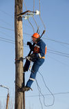 Electrician working at height with wires Royalty Free Stock Image