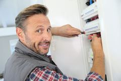 Electrician working on installations. Electrician fixing electric panel in private home Royalty Free Stock Image