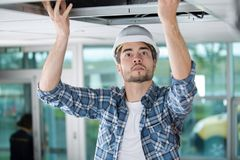 Electrician working through open ceiling hatch royalty free stock photography