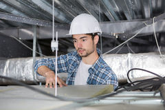 Electrician working through open ceiling hatch Stock Image