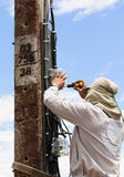 Electrician working on power poles. Daytime Royalty Free Stock Photos