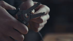 Electrician working on wiring using a pair of pliers to strip Royalty Free Stock Images