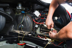 Electrician works with electric block in car. Close-up of automobile inside under raised hood. Service man hands working with cables of auto Stock Photos