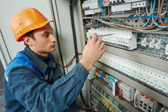 Electrician works with electric meter tester in fuse box Royalty Free Stock Photo
