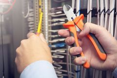 Electrician works in electrical fuse box with electric tools. Electrician works in electrical fuse box with electric tools royalty free stock photo