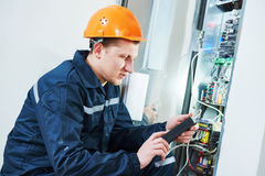 Electrician works with electronic equipment Royalty Free Stock Image