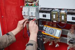 Electrician measurements with multimeter tester. Electrician works. male technician examining fusebox with digital multimeter ac dc tester stock image