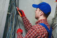 Electrician works with switchbox stock image