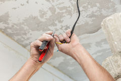 Electricians cleans the contacts with pliers. Installing the ceiling light.  Royalty Free Stock Photos