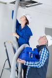 Electricians fitting ac hoses in buildings ceiling. Male royalty free stock photos