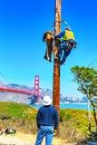 Electricians hang a scarecrow of a man on a pole. San Francisco, California, USA - September 10, 2018: Electricians hang a scarecrow of a man on a pole stock photo