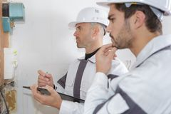Electricians installing circuit breaker. Trainee Royalty Free Stock Image
