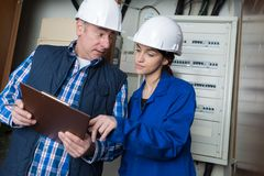 Electricians installing distribution board. Electricians installing a distribution board stock photos