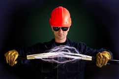 Electricians. In insulating gloves keeps cables that shoot lightning stock images