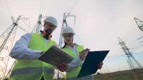 Electricians male and female discussing electrical equipment near power line. Electricians male and female discussing electrical equipment. 4K stock video footage