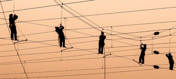 Electricians repair contact wire at sunset. Electricians repair contact wire on electrified railway at sunset Royalty Free Stock Image