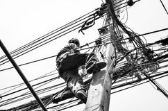 Electricians repairing wire at climbing work on electric post power pole. Black and white image Royalty Free Stock Photography