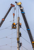 Electricians repairing wire on electricity power pole with hydraulic platform. Stock Photos