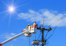 Electricians repairing wire of the power line with bucket hydraulic lifting platform. On blue sky background Royalty Free Stock Photos
