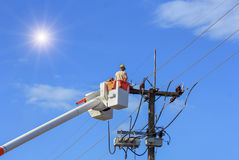 Electricians repairing wire of the power line with bucket hydraulic lifting platform Stock Photography
