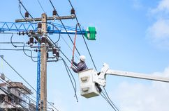 Electricians repairing wire of the power line with bucket hydraulic lifting platform. On blue sky stock photos