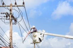 Electricians repairing wire of the power line with bucket hydraulic lifting platform. On blue sky stock photo