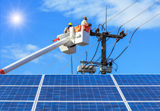 Electricians repairing wire of the power line on bucket hydraulic lifting platform with photovoltaics in solar power station. On blue sky with sunlight Royalty Free Stock Photos