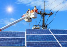 Electricians repairing wire of the power line on bucket hydraulic lifting platform with photovoltaics in solar power station. On blue sky with sunlight Royalty Free Stock Images